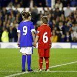 Children wearing Everton and Liverpool jerseys pay their respects to the 96 victims of the Hillsborough disaster before the English Premier League soccer match between Everton and Newcastle United at Goodison Park in Liverpool
